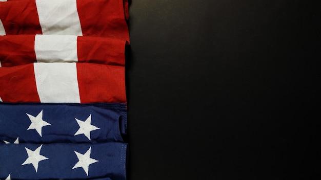 Zbliżenie macha amerykańską flagę narodową usa na czarnym tle z miejsca kopiowania tekstu.