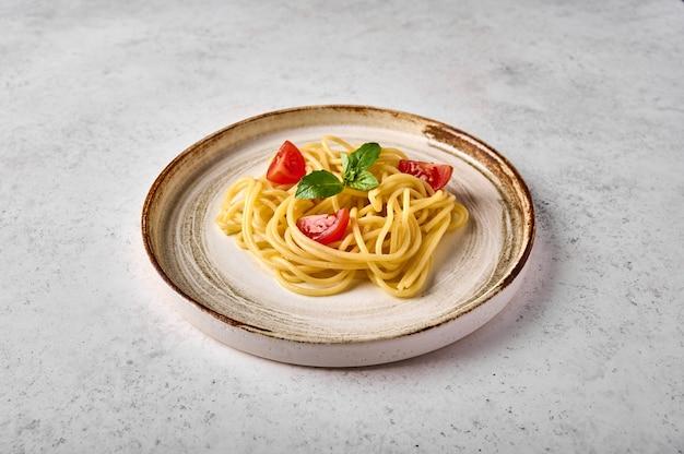 Zbliżenie makaron spaghetti z serem pomidorowo-wiśniowym z parmezanem i bazylią na talerzu ceramicznym na światło