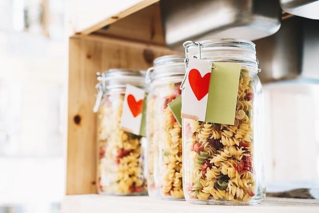 Zbliżenie makaron w szklanych słoikach na tle wnętrza sklepu zero waste. obraz zakupów w małych firmach. nowy trend alternatywnych zakupów. koncepcja plastikowego wolnego sklepu spożywczego.