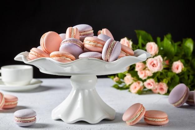 Zbliżenie makaroniki na białym stojaku na ciasto. piękny bukiet róż i filiżanka kawy na czarnej powierzchni, wolna przestrzeń