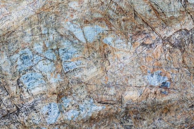 Zbliżenie makro pęknięty kamień powierzchni brązowy, szary, niebieski kolor. szczegółowa tekstura wzór natura, tło zrobione w środowisku naturalnym. zwietrzały przez lata, niepowtarzalny efekt teksturowanej konstrukcji.