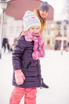 Zbliżenie mała dziewczynka cieszy się łyżwiarstwo z jej ojcem