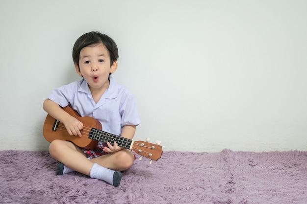 Zbliżenie małe dziecko w studenckim mundurze bawić się ukulele na dywanie z kopii przestrzenią