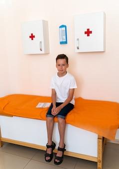 Zbliżenie małego chłopca czeka na sprawdzenie w gabinecie lekarskim. dziecko idzie do pediatry na regularne wizyty.
