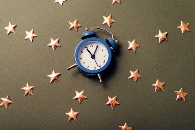 Zbliżenie małego niebieskiego zegara między wieloma gwiazdami na ciemnym stole