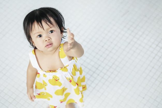 Zbliżenie małej dziewczynki spojrzenie jak ona chce coś na białej kafelkowej podłoga textured tło