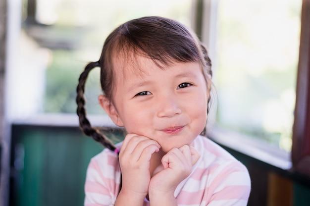Zbliżenie małej dziewczynki uśmiechu azjatykcia twarz, mały szczęśliwy uśmiechnięty powabny model