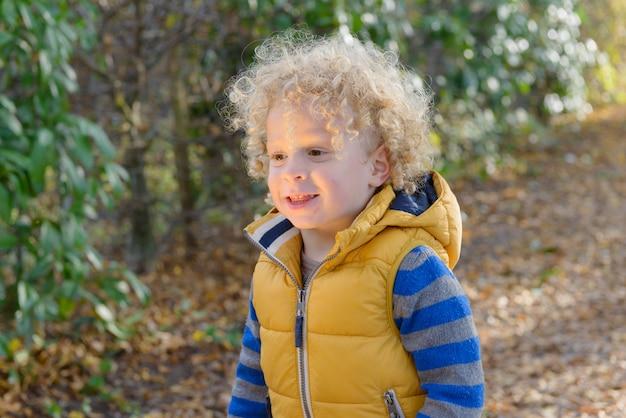 Zbliżenie mały ładny chłopiec z blond kręcone włosy, stojąc