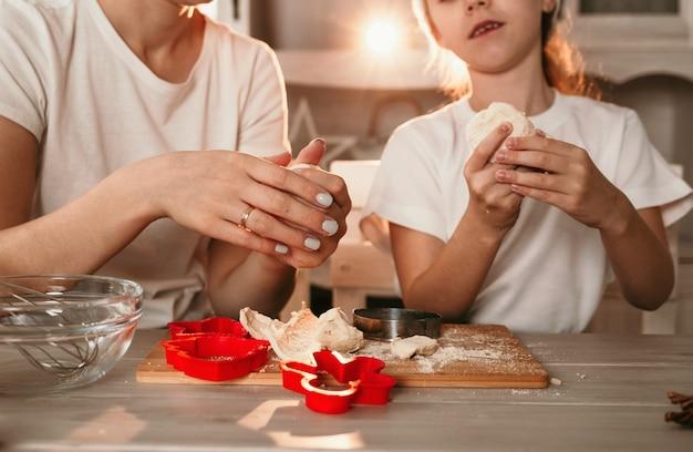 Zbliżenie mama i córka gotują ciasteczka z ciasta na kuchennym stole