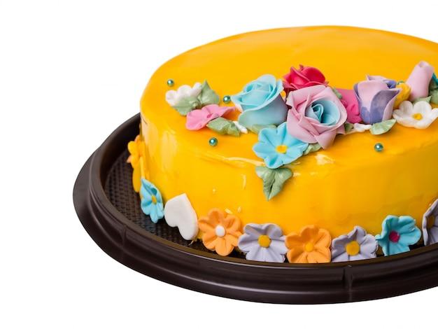 Zbliżenie mangowe dżemu torta dekoracje z colourful lukrowymi owoc na białym tle