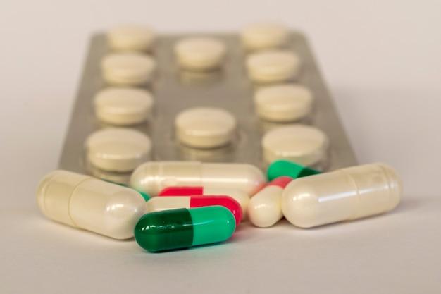 Zbliżenie manipulowanych kapsułek leków z rozmytym tłem i miejscem na tekst