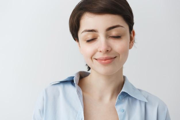 Zbliżenie: marzycielska atrakcyjna dziewczyna zamyka oczy i uśmiecha się, marzy o czymś przyjemnym