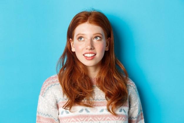 Zbliżenie: marzycielska nastolatka z rudymi włosami, patrząc w lewym górnym rogu i uśmiechnięta, stojąca na niebieskim tle.