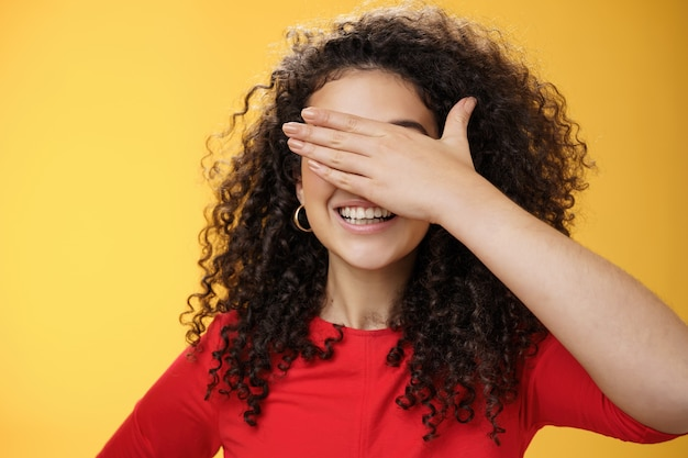 Zbliżenie marzycielski szczęśliwy młoda śliczna kobieta z kręconymi włosami zakrywającymi oczy dłonią, jak liczenie lub gra w peekaboo uśmiechający się szeroko przewidując niespodziankę na żółtym tle.