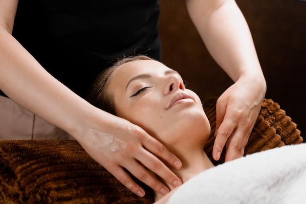 Zbliżenie masażu twarzy w centrum spa. dziewczyna z idealną skórą relaks w gabinecie masażu.