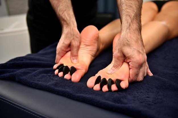 Zbliżenie: masażysta daje masaż ajurwedyjski gorącymi kamieniami na kobiece stopy. masaż gorącymi kamieniami