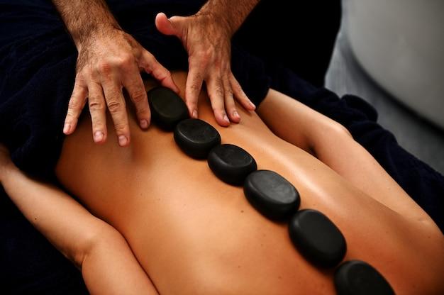 Zbliżenie: masażysta układa gorące kamienie wzdłuż kręgosłupa młodej kobiety i robi ajurwedyjski masaż gorącymi kamieniami w nowoczesnym salonie spa