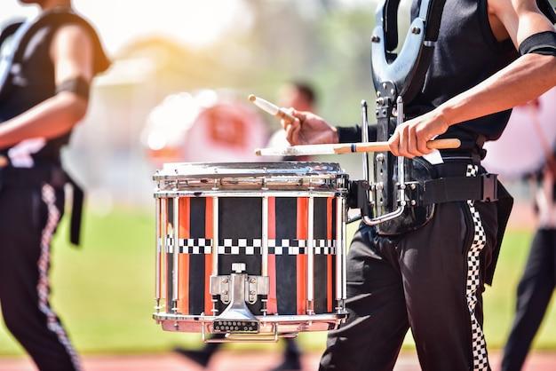 Zbliżenie maszerujących perkusistów orkiestry