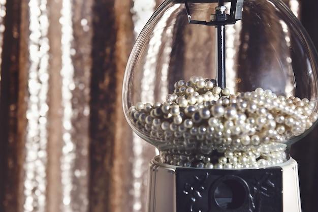 Zbliżenie maszyny dozownika cukierków w kształcie pereł z przezroczystego szkła