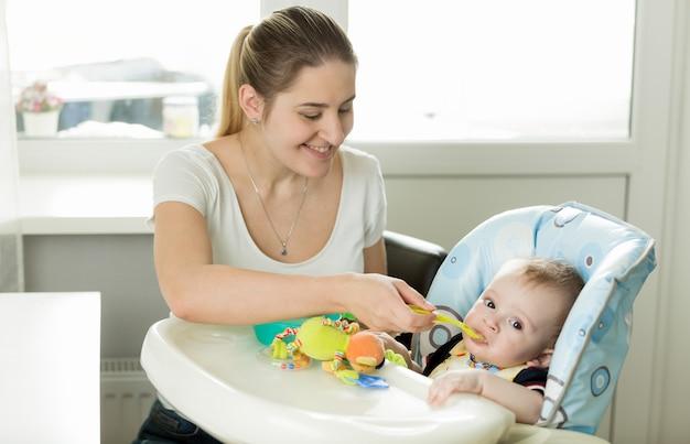 Zbliżenie matki dającej owsiankę chłopcu z plastikowej łyżki