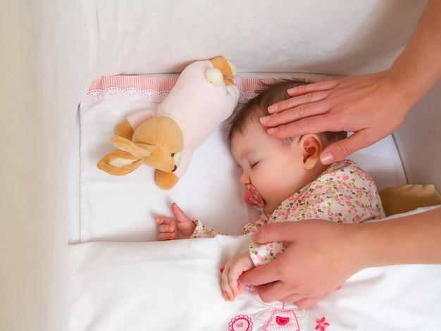 Zbliżenie matki pieszczącej jej śliczną córeczkę śpiącą w łóżeczku ze smoczkiem i pluszową zabawką