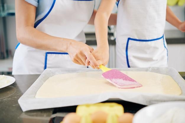 Zbliżenie matki pomagającej córce rozprowadzać płynne ciasto na blasze do pieczenia za pomocą silikonowej szpatułki