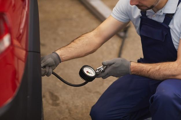 Zbliżenie mechanika samochodowego sprawdzanie ciśnienia w oponach podczas kontroli pojazdu w sklepie garażowym, kopia przestrzeń