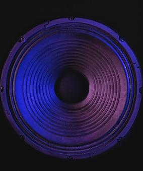 Zbliżenie membrany głośnika na czarnym tle z kolorowym oświetleniem.