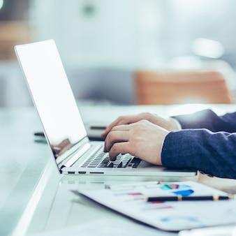 Zbliżenie - menedżerowie finansowi pracujący na laptopie z danymi finansowymi w miejscu pracy w nowoczesnym biurze.
