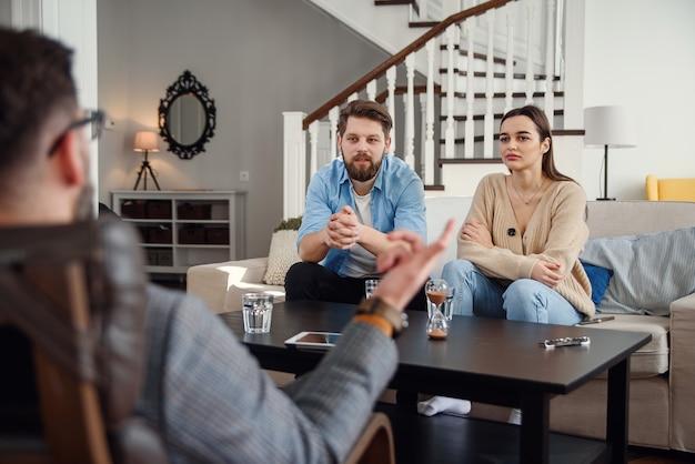Zbliżenie męski psycholog siedzi przy krześle i słucha przygnębionej młodej pary w stylowym przytulnym biurze. selektywne ustawianie ostrości.