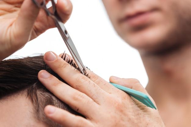 Zbliżenie męskich dłoni z nożyczkami i grzebieniem nad głową klienta