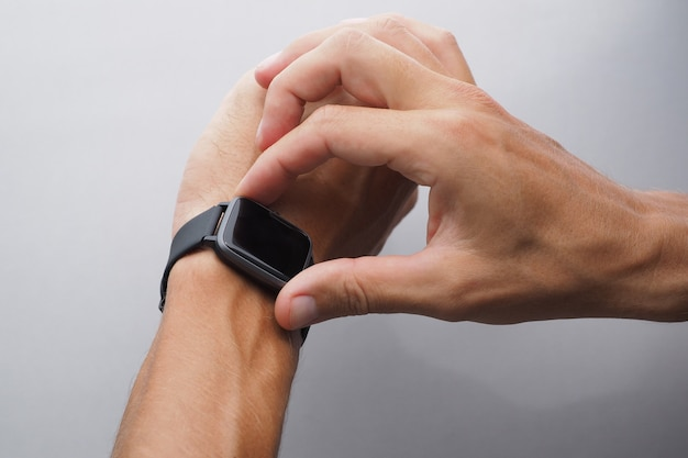 Zbliżenie męskich dłoni z opaloną skórą korzysta z inteligentnego zegarka