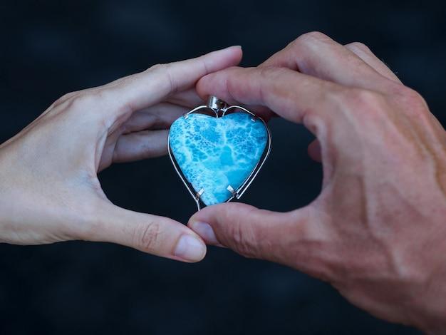 Zbliżenie męskich i żeńskich rąk trzymających kamień larimar w formie serca. koncepcja miłości. selektywne ustawianie ostrości.