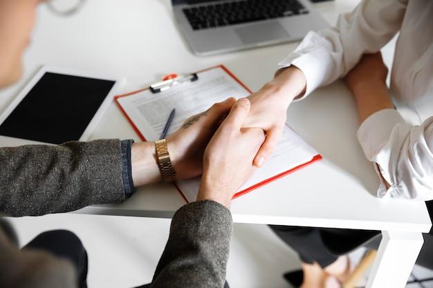 Zbliżenie męskich i żeńskich rąk trzymających się przy stole z arkuszami laptop smartphone office