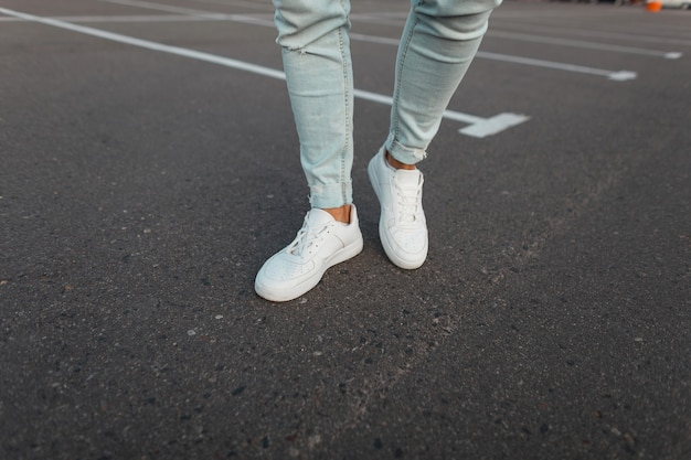 Zbliżenie męskich nóg. modny młody modny mężczyzna w vintage niebieskie dżinsy w skórzane stylowe białe trampki stoją na asfaltowej drodze na zewnątrz. nowoczesny, młodzieżowy styl uliczny.