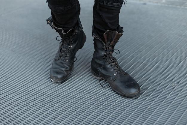Zbliżenie męskich nóg. stylowy młody człowiek w modnych dżinsach w czarnych skórzanych butach vintage. szczegóły codziennego wyglądu. staroświecki styl. zbliżenie.
