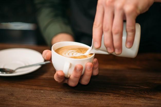 Zbliżenie męskich rąk, dodając śmietankę do kawy.