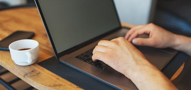 Zbliżenie męskich rąk pisania na laptopie. panoramiczny widok na baner.