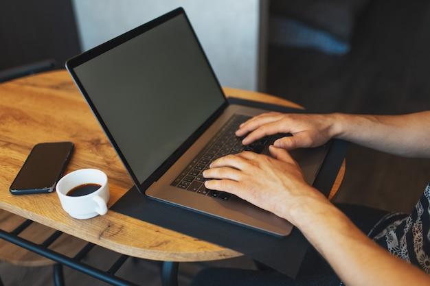 Zbliżenie męskich rąk pracujących na laptopie smartphone i filiżankę kawy na drewnianym stole.