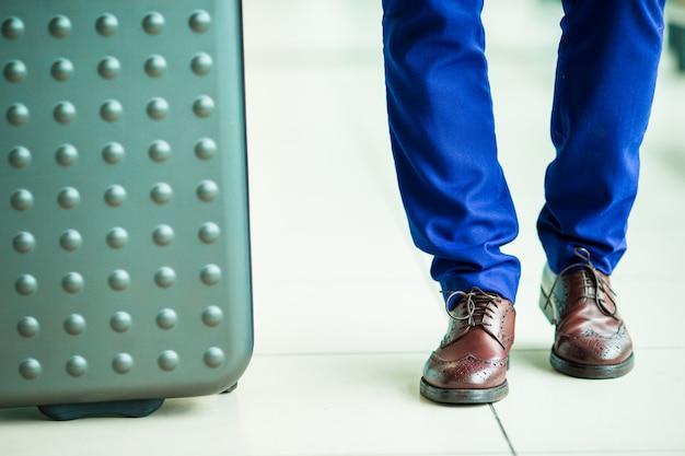 Zbliżenie: męskie buty i bagaż na lotnisku. młody turystyczny mężczyzna przy lotniskiem przygotowywającym dla podróżować