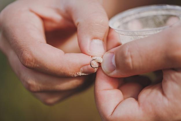Zbliżenie męskie ręce trzymają małe pudełko z robakami i zakładają przynętę na haczyk, aby łowić wędką na rozmytym pastelowym brązowym tle. styl życia, rekreacja, koncepcja wypoczynku. rybak z robakiem.