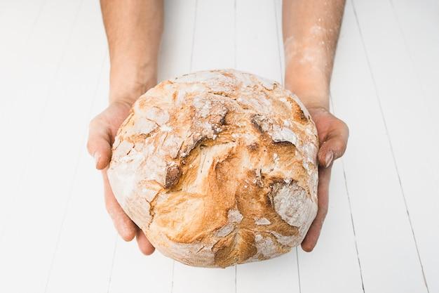 Zbliżenie męskie ręki stawia świeżego chleb na starym wieśniaka stole na czarnym tle z kopii przestrzenią dla twój teksta