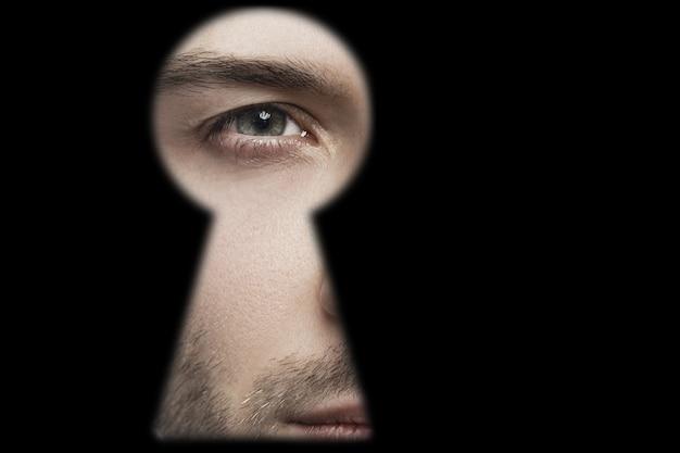 Zbliżenie męskiego oka patrzącego w dziurkę od klucza