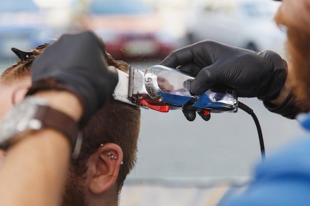 Zbliżenie męskiego profesjonalnego fryzjera obsługującego klienta przez maszynkę do strzyżenia