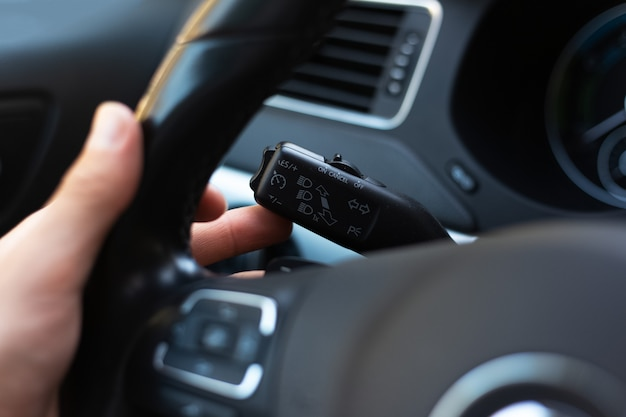 Zbliżenie męskiej dłoni, naciska przycisk przełącznika sygnału w samochodzie.