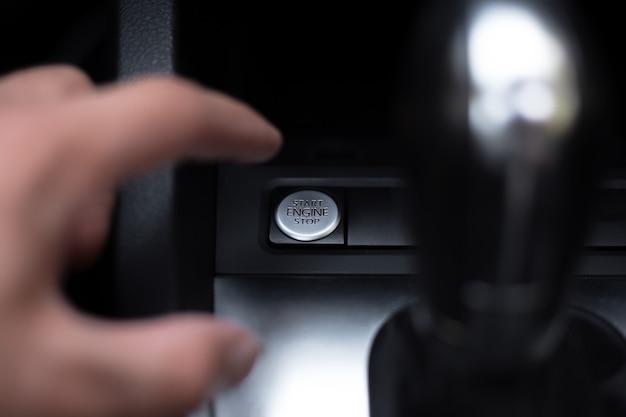 Zbliżenie męskiej dłoni, naciska przycisk uruchamiania i zatrzymywania silnika w samochodzie.