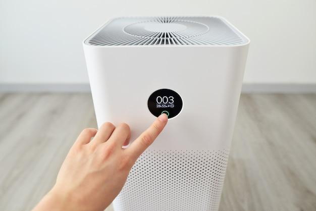 Zbliżenie męskiej dłoni naciskając przycisk na oczyszczaczu powietrza oczyszczacz powietrza w pomieszczeniach z monitorem cyfrowym
