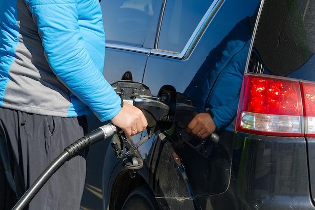 Zbliżenie męskiej dłoni napełniającej czarny samochód olejem napędowym z pompą gazową