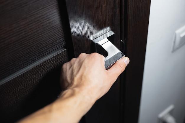 Zbliżenie męskiej dłoni otwierającej drzwi