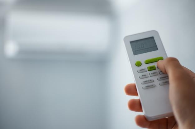 Zbliżenie męskiej dłoni za pomocą zdalnego sterowania klimatyzatorem typu split.